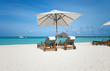 sun loungers under white umbrella on sandy beach