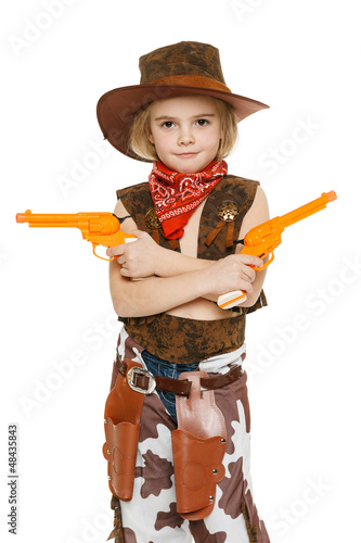 Little girl with wearing cowboy costume holding guns