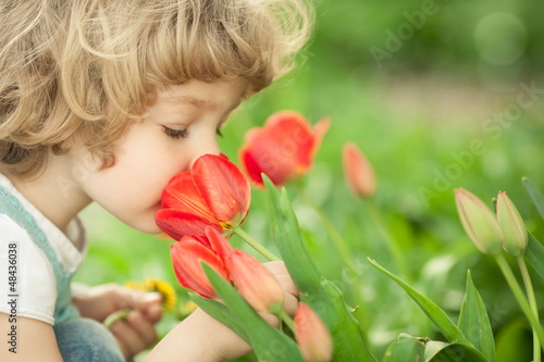Child smelling tulip