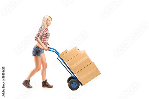 Female worker pushing a hand truck with boxes