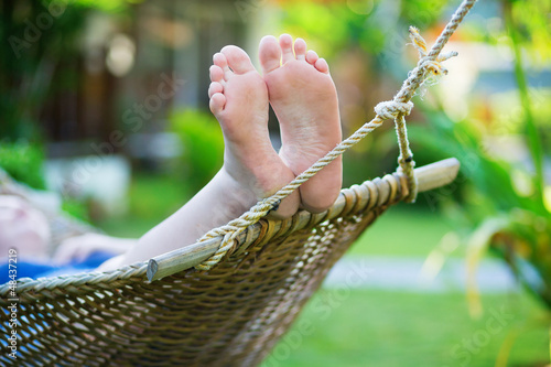 Woman relaxing in hammock on a tropical resort