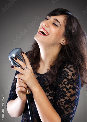 Attractive young  woman with a retro microphone