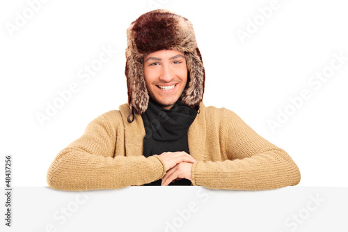 Handsome young man with fur hat posing behing a panel