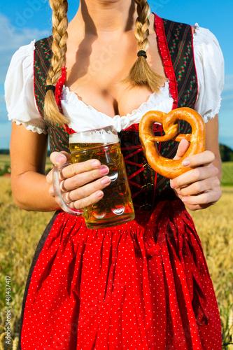 Weiblicher Körper ohne Kopf mit Bier und Brezel