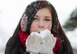 Girl blowing fluffy snowflakes