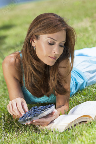 Woman Outside Eating Blueberries & Reading Book