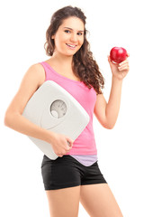 Young female holding an apple and a weigh scale