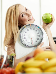 Girl with scale and fruits in the kitchen is proud to lose weigh