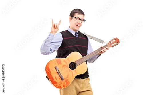 Man with a guitar making a rock and roll hand sign