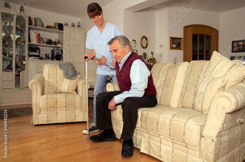 Pflegekraft hilft Senior beim Aufstehen