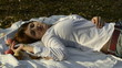 Young woman lying on bedspread in autumn park