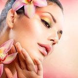 Fototapety Beautiful Spa Girl With Orchid Flowers Touching her Face