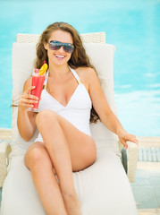 Happy young woman in swimsuit relaxing with cocktail