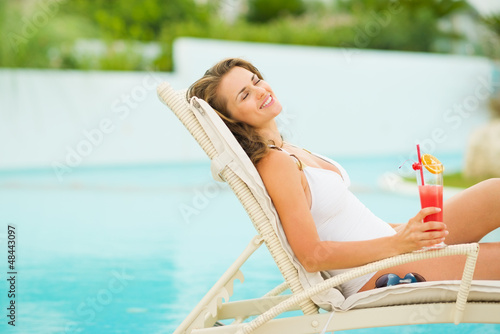 Young woman in swimsuit relaxing with cocktail on chaise-longue