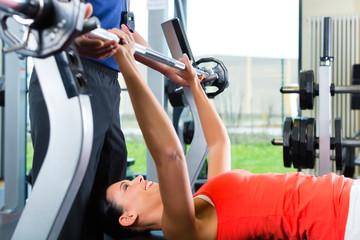 Trainer und Frau im Fitnessstudio