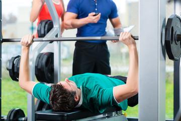 Trainer und Mann im Fitnessstudio