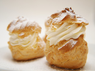Choux pastry buns, filled with whipped cream, on a plate