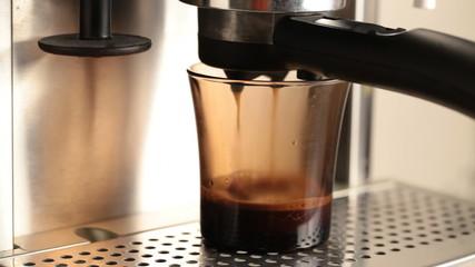 Coffee pours in dark glass cup in espresso coffee machine