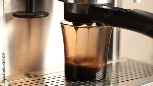 Coffee pours in dark glass cup in espresso coffee machine
