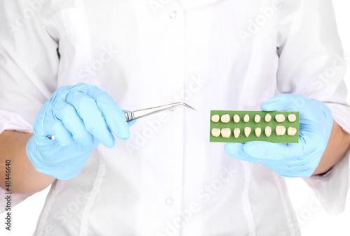 Dentists hands with denture and dental tweezers