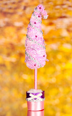 Christmas tree with curved tip on bright background
