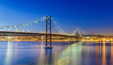 Fototapety Night view of Lisbon and of the 25 de Abril Bridge, Portugal