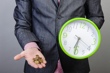 Young businessman holding money and watch
