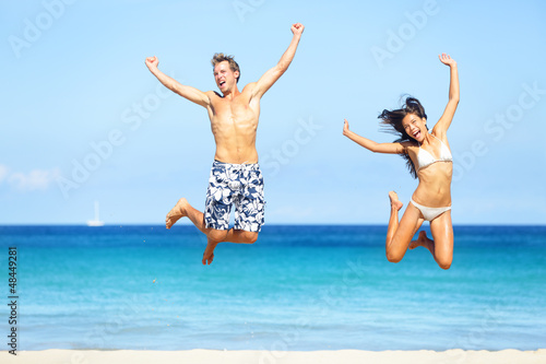 Beach people - happy couple jumping