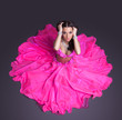 Pretty dancer in pink costume sitting on floor
