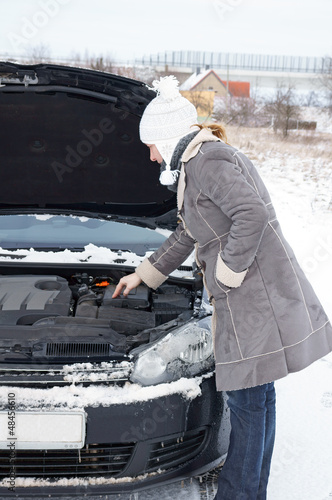 Car break - woman looks into the engine compartment