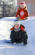 Children slide down icy hill