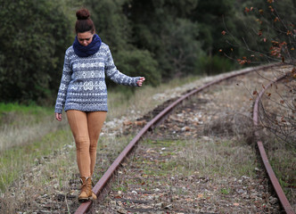 Chica joven hace equilibrio en las vias del tren