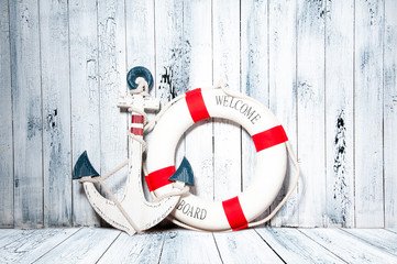 Anchor and life buoy on a background of white wall.