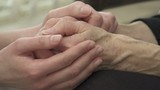 young hands comforting older hands