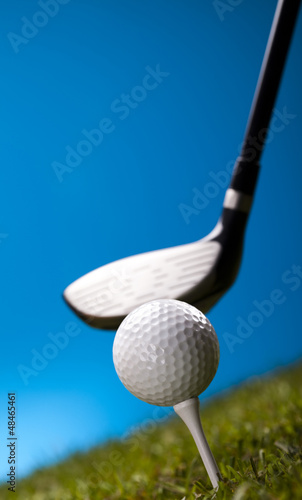 Golf ball on green grass over a blue background