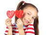 Child holding heart shaped candy