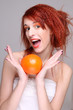 funny redhaired woman with orange in her hands
