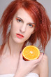 redhaired woman with orange half in her hand