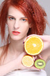 redhaired woman with orange, lemon and kiwi