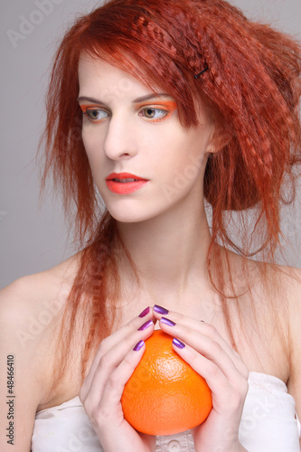 curly redhaired girl with orange in her hands