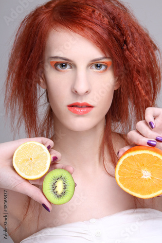 redhaired girl with orange, lemon and kiwi