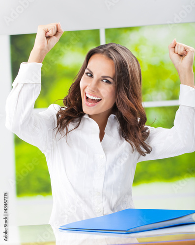 Happy gesturing smiling young businesswoman