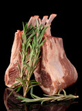 Raw rack of lamb, isolated on black with rosemary