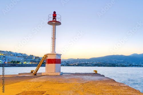 Lighthouse of Agios Nikolaos city at sunset on Crete, Greece