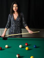Beautiful brunette playing pool