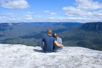 Couple sitting on top of mountain