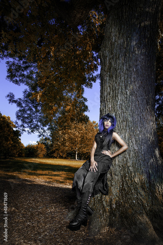 Sexy black gothic woman by tree