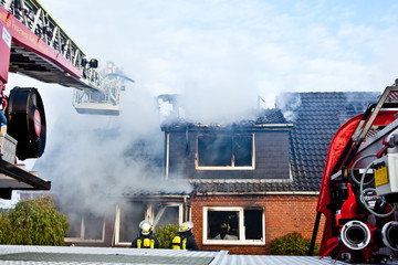 Firefighters turntable ledder at house fire