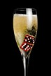 champagne flute with golden bubbles and red dice