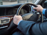 Chauffeur's hands on the steering wheel of a luxury car
